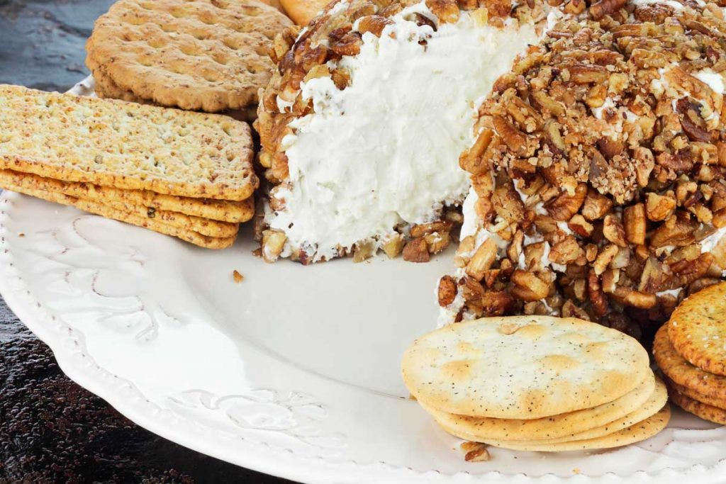 A walnut encrusted classic cheese ball on a plate with crackers.